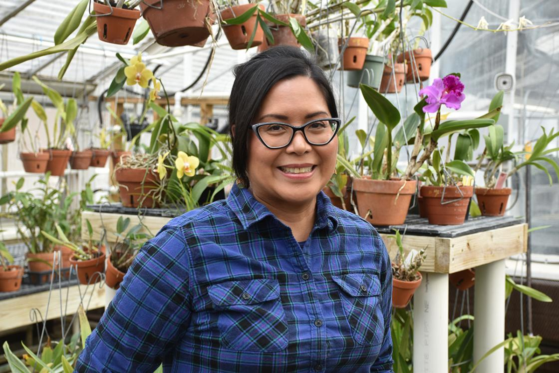 Photograph of a smiling volunteer in the Conservatory Greenhouse at Cranbrook House & Gardens.