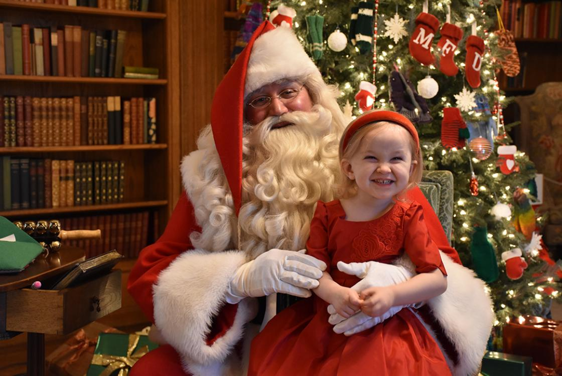 Photograph of a girl visiting with Santa during Holiday Splendor at Cranbrook House, December 2018.