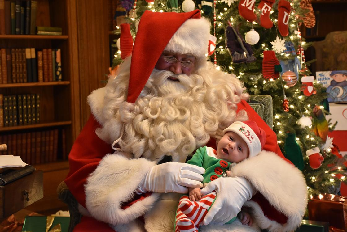 Photograph of Santa with a baby during Holiday Splendor at Cranbrook House, December 2018.