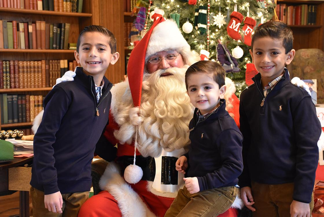 Photograph of three boys with Santa at Cranbrook House during Holiday Splendor, December 2018.