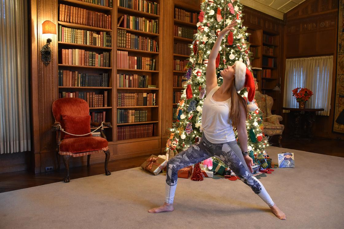Photograph of a woman practicing yoga in the Cranbrook House Library during Holiday Splendor 2018.