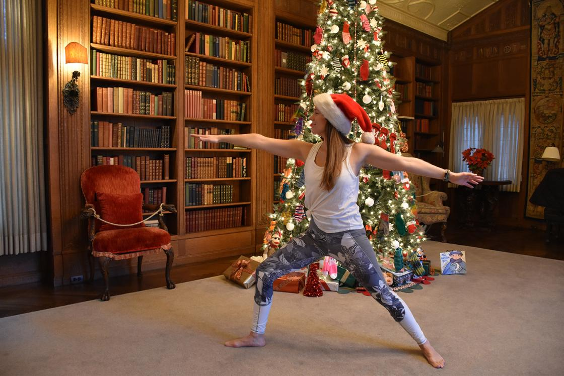 Photograph of a woman in a Santa hat practicing yoga at Cranbrook House during Holiday Splendor 2018.