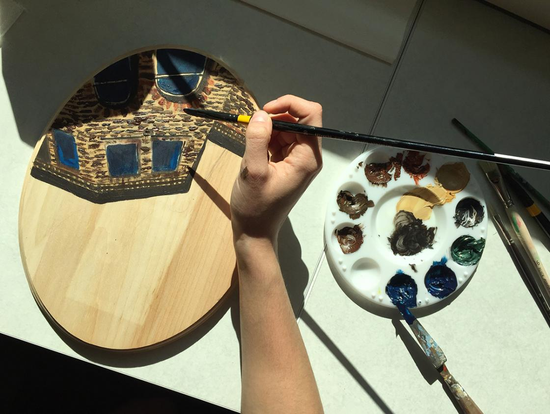 Photograph of a student painting a cartouche in the Cranbrook Art Museum Art Lab, October 2018.